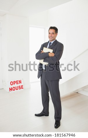 Full length portrait of a smiling businessman with documents at an house for sale - stock photo
