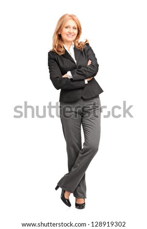 Full length portrait of a smiling businesswoman leaning on wall isolated on white background - stock photo