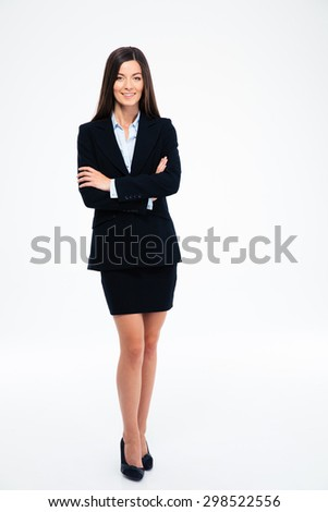 Full length portrait of a smiling businesswoman standing with arms folded isolated on a white background. Looking at camera - stock photo