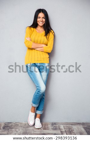 Full length portrait of a smiling casual woman standing with arms folded on gray background. Looking at camera - stock photo