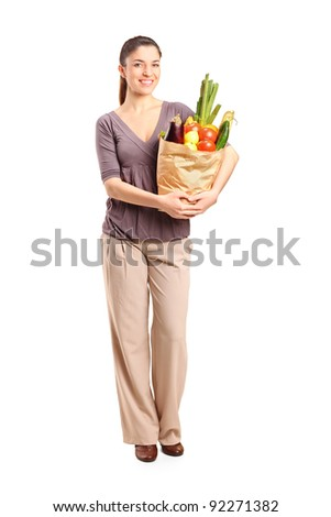 Full length portrait of a smiling female holding a paper bag full of groceries isolated on white background - stock photo