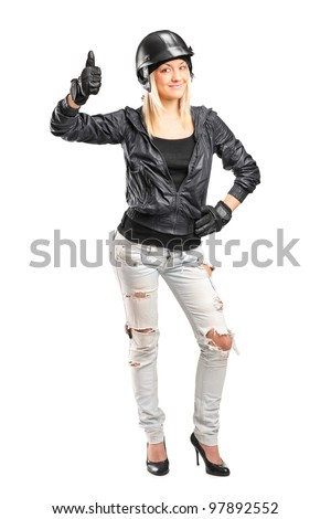 Full length portrait of a smiling female motorcycler giving a thumb up isolated on white background