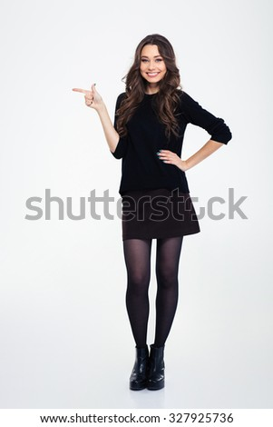 Full length portrait of a smiling girl pointing finger away isolated on a white background - stock photo