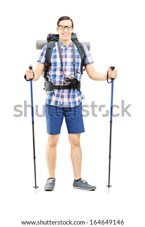 Full length portrait of a smiling hiker with backpack and hiking poles posing isolated against white background