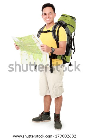 Full length portrait of a smiling male hiker with backpack and map isolated on white background - stock photo