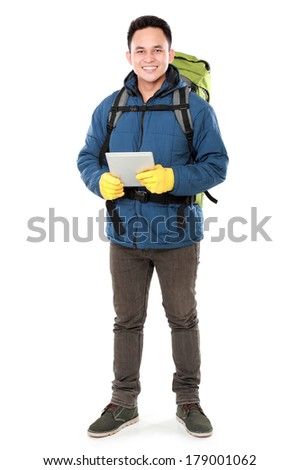 Full length portrait of a smiling male hiker with backpack using tablet computer isolated on white background