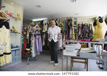 Full length portrait of a smiling male owner in clothing store - stock photo