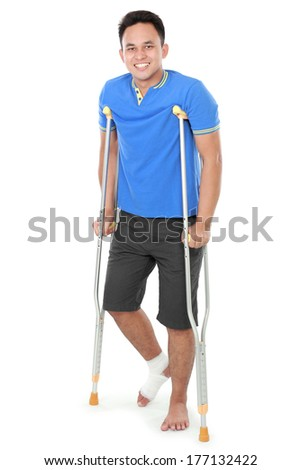 Full length portrait of a smiling male with broken leg using crutch isolated on white background - stock photo