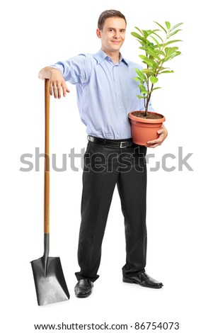 Full length portrait of a smiling man holding a plant and a shovel isolated on white background - stock photo