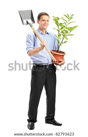 Full length portrait of a smiling man holding a potted plant and a shovel isolated on white background - stock photo