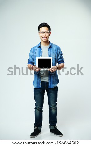 Full length portrait of a smiling man showing tablet computer screen on gray background - stock photo