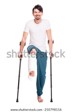 Full length portrait of a smiling man with broken leg is using crutch isolated on white background. - stock photo