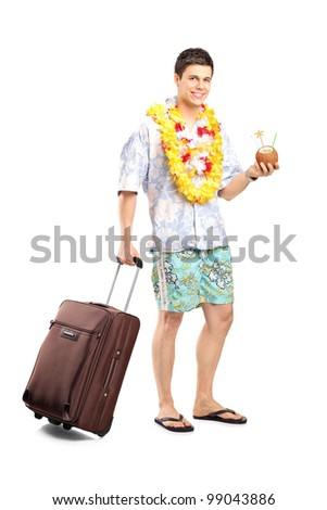 Full length portrait of a smiling man with cocktail carrying his luggage isolated on white background - stock photo