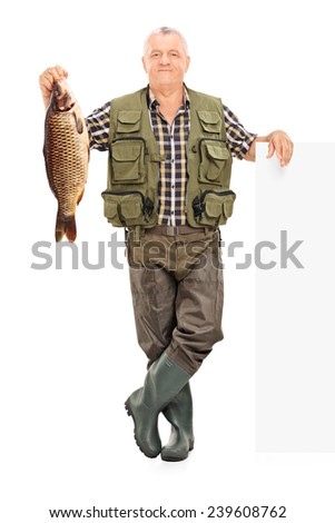 Full length portrait of a smiling mature fisherman holding a fish next to a panel isolated on white background - stock photo
