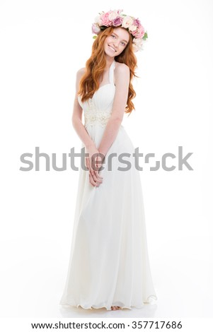Full length portrait of a smiling redhead woman with wreath from flowers on head standing isolated on white background - stock photo