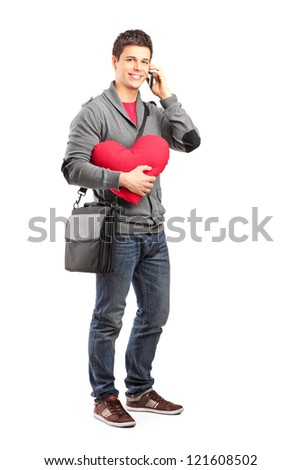 Full length portrait of a smiling student holding a red heart and talking on a phone isolated on white background - stock photo