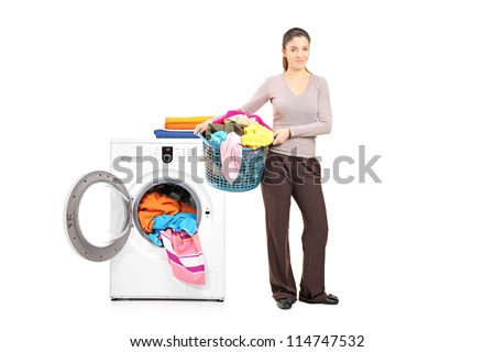 Full length portrait of a smiling woman holding a laundry basket next to a washing machine isolated on white - stock photo
