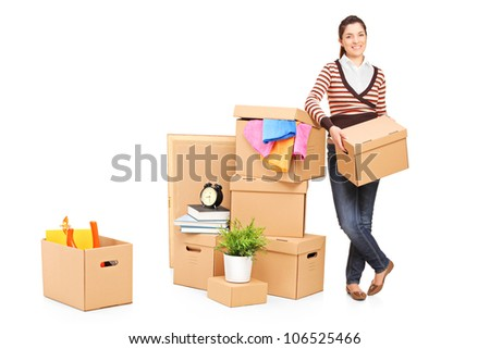 Full length portrait of a smiling woman moving into a new home with many boxes around her