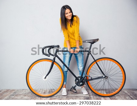 Full length portrait of a smiling woman standing near bicycle on gray background. Looking at camera - stock photo