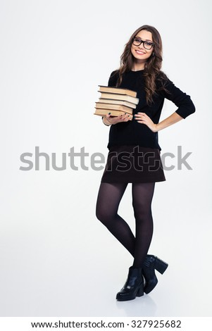 Full length portrait of a smiling woman standing with books isolated on a white background and looking at camera - stock photo