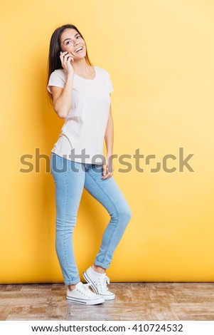 Full length portrait of a smiling woman talking on the phone over yellow background - stock photo