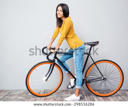 Full length portrait of a smiling woman with bicycle on gray background. Looking at camera - stock photo
