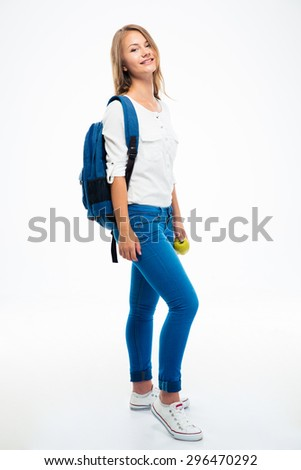 Full length portrait of a smiling young girl with backpack and apple standing isolated on a white background - stock photo