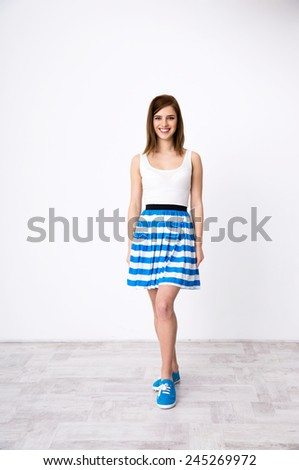 Full length portrait of a smiling young woman posing at studio - stock photo