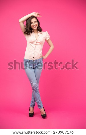 Full length portrait of a smiling young woman posing over pink background. Wearing in jeans and shirt. Looking at camera - stock photo