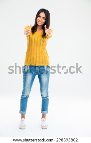 Full length portrait of a smiling young woman showing thumbs up isolated on a white background - stock photo
