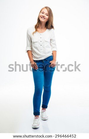 Full length portrait of a smiling young woman standing isolated on a white background. Looking at camera - stock photo