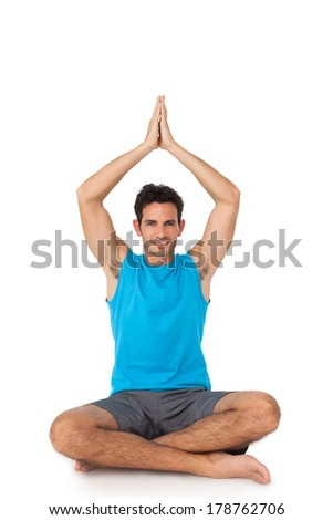 Full length portrait of a sporty young men in meditation pose over white background - stock photo