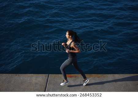 Full length portrait of a sporty young woman running along the beach with amazing big ocean waves on background - stock photo