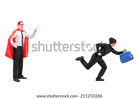 Full length portrait of a superhero chasing a burglar isolated on white background - stock photo