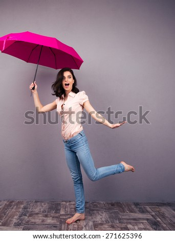 Full length portrait of a surprised woman posing with pink umbrella in studio. Wearing in jeans and shirt. Barefoot. Looking at camera  - stock photo