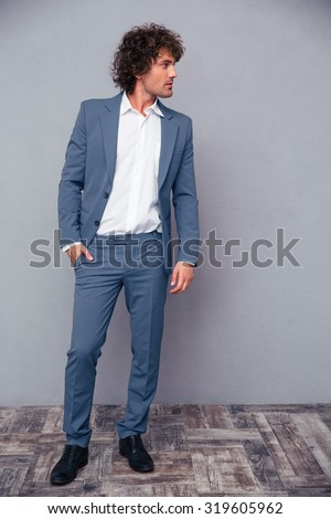 Full length portrait of a thoughtful businessman looking away on gray background - stock photo