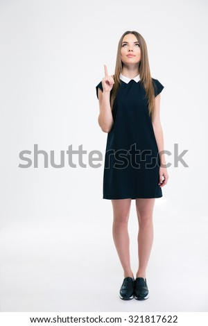 Full length portrait of a thoughtful woman pointing finger up at copyspace isolated on a white background - stock photo