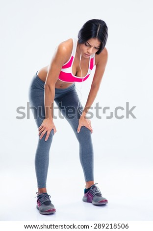 Full length portrait of a tired fitness woman resting over gray background - stock photo