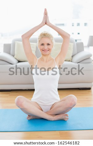 Full length portrait of a toned young woman sitting with joined hands over head at fitness studio