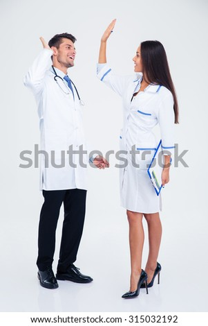 Full length portrait of a two medical workers giving five isolated on a white background - stock photo