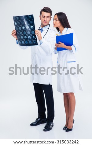 Full length portrait of a two medical workers looking at x-ray picture of brain isolated on a white background - stock photo