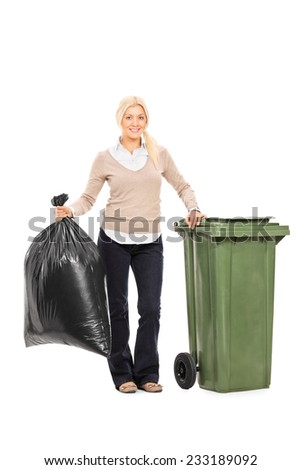 Full length portrait of a woman holding a trash bag next to a garbage bin isolated on white background - stock photo