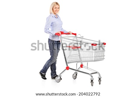 Full length portrait of a woman pushing a shopping trolley isolated on white background - stock photo