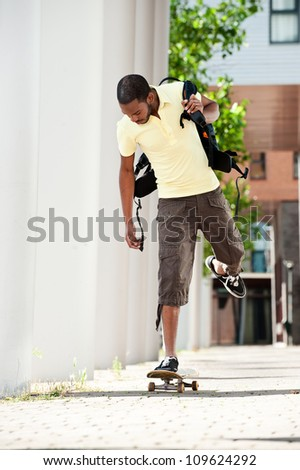 Full length portrait of a young African American male student skateboarding to class on campus - stock photo