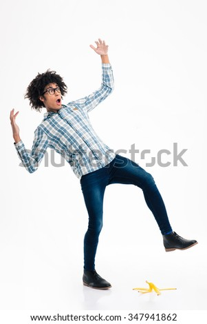 Full length portrait of a young afro american man slipping on banana skin isolated on a white background - stock photo