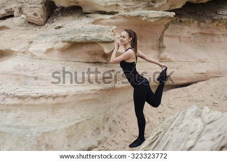 Full length portrait of a young athletic female with perfect figure dressed in sportswear doing physical exercises in mountain landscape,healthy fit woman stretching legs before began her run outdoors - stock photo