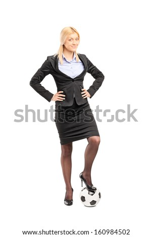 Full length portrait of a young blond businesswoman in high heels posing with a soccer ball isolated on white background - stock photo