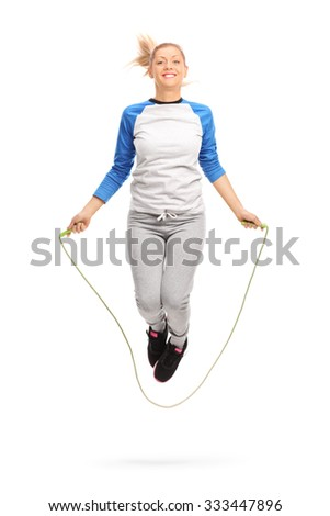 Full length portrait of a young blond girl exercising with skipping rope shot in mid-air isolated on white background - stock photo