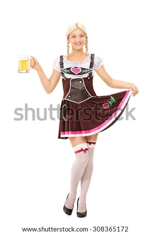 Full length portrait of a Young blond woman in Bavarian costume holding a pint of beer and looking at the camera isolated on white background