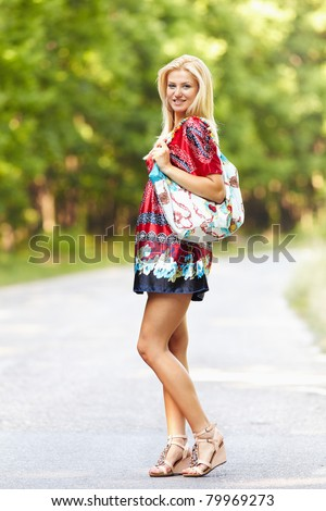 Full length portrait of a young blond woman in colorful dress with purse outdoor - stock photo